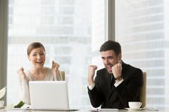 Young business leaders excited because of success. Happy female and male managers or business partners screaming with joy when sitting at desk and looking on Stock Photo