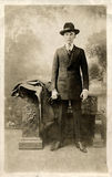 Young Business Man. Early 1900 portrait of a young man in a suit and Fedora hat holding a cigar in one hand and gloves in the other royalty free stock image