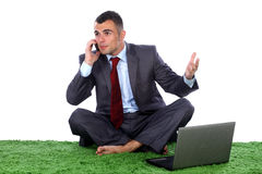 Young business man. Barefoot siting on a green carpet with lap top in front of him talking on a mobile phone Royalty Free Stock Photos