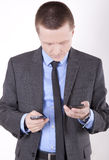 Young business man. Checking his smartphones Royalty Free Stock Photos