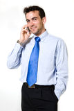 Young business man. Attractive brunette young business man wearing blue shirt and tie standing on white talking on a cellular phone Royalty Free Stock Images