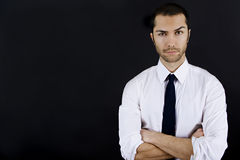 Young business man. With his arms crossed and raised eyebrow Royalty Free Stock Photo