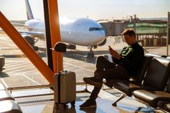 Young business man in airport using smartphone. stock photography