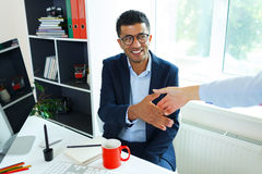 Young business man with arm extended to handshake. Modern young business men with arm extended to handshake Royalty Free Stock Photo