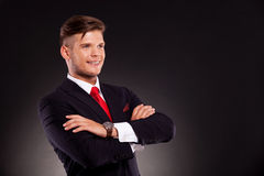 Young business man with arms crossed. Handsome young business man standing with arms crossed and smiling, while looking away from camera. on dark background Royalty Free Stock Photo