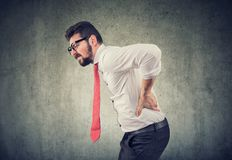 Young business man with backache. Young business man with lower back pain on gray wall background royalty free stock images