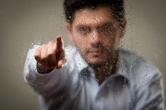 Young business man, behind a blurred window with drops, pointing in from of him his hand, gray background.  Royalty Free Stock Photography