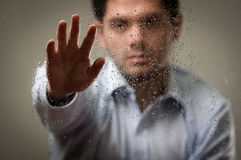 Young business man, behind a blurred window with drops, pointing in from of him an open hand, gray background.  Royalty Free Stock Image