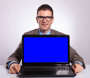 Young business man behind a laptop with blue screen. Young business man smiling from behind a laptop with a blue screen. on a gray background Royalty Free Stock Photography
