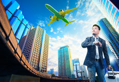 Young business man and belonging luggage standing against building urban scene looking to sky with passenger jet plane flying. Above use for people in traveling royalty free stock image