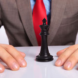 Young business man with the black chess king. Closeup of a black chess king between the hands of a young business man . on a gray background Royalty Free Stock Photos