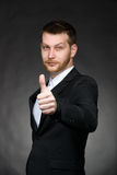 Young business man in black suit with thumbs up Stock Images
