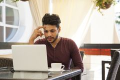 Young business man Blogger sitting at laptop, smartphone and cup. Of coffee. Student learning online royalty free stock images