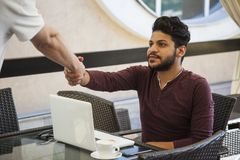 Young business man Blogger sitting at laptop, smartphone and cup. Of coffee. Student learning online stock photography