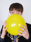 Young business man blowing up a yellow balloon Royalty Free Stock Images