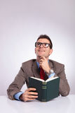 Young business man with book in hand is daydreaming Royalty Free Stock Photography