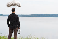 Young business man with briefcase and storm cloud, concept of business problems Royalty Free Stock Photography