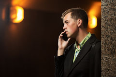 Young business man calling on mobile phone at the wall Royalty Free Stock Photo