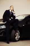 Young businessman calling on cell phone by car Stock Image
