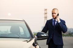 Young business man calling on the phone next to car Royalty Free Stock Photography