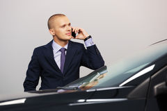 Young businessman calling on cell phone by car Stock Photo