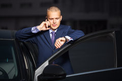 Young businessman calling on cell phone by car Stock Photography