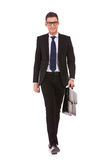 Young business man carrying a suitcase, walking Stock Images