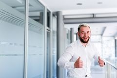 Young Business Man Celebrate Success. Young Handsome Business man Standing At Company`s Indoor Stock Image