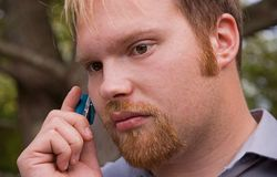Young Business Man on Cell Phone. This young Caucasian business man with red hair and goatee is in conversation on his teal colored cell phone Stock Images