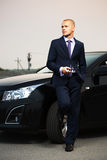 Young business man with a cell phone at the car Stock Photography