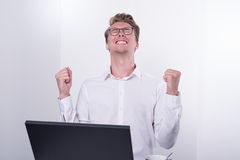 Young business man cheering his success while working on laptop royalty free stock images