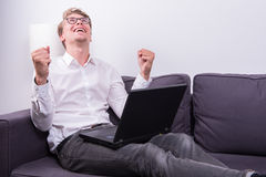Young business man cheering his success while working on laptop Royalty Free Stock Image