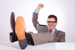 Young business man cheers with tablet and feet on desk. Young business man reading something on his tablet and cheering while holding his feet on his desk. on a Stock Images