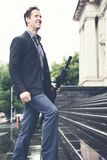 Young business man climbing steps on way to work looking up Royalty Free Stock Photography