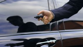 Young business man closing his car door with remote control key, close up. Stock footage stock video footage