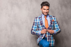 Young business man closing his jacket. Young business man smiling to the camera while closing his jacket Royalty Free Stock Images