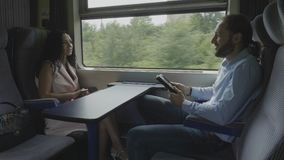 Business man commuting from work to home using a tablet pc talking and flirting with elegant attractive young woman during travel. Young business man commuting stock video footage