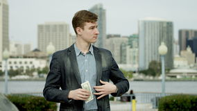 Young business man is counting his money on a street of Coronado, San Diego. Young businessman is standing on a street of Coronado, San Diego and counting his stock video footage