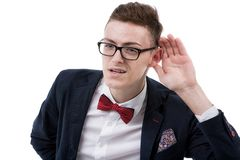 Young business man cupping hand behind ear on white background - Stock Photos