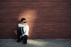 Young business man in depression sitting at the wall Stock Image