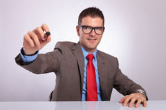 Young business man at desk, writes with marker Royalty Free Stock Images
