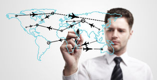 Young business man drawing an airplane routes royalty free stock photos
