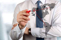 Young business man drawing an airplane routes on world map. Stock Images