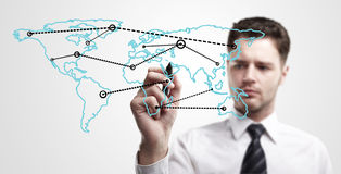 Young business man drawing a global network