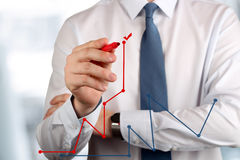 Young business man drawing  a graphs by red pen Stock Images