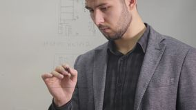 Young business man drawing a project of building on a glass window. Portrait of young architect thinking about. Construction. On a white background stock video