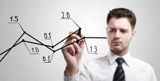 Young business man drawing a rise graph Stock Photos