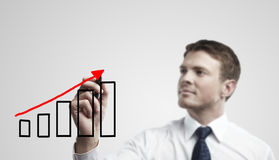 Young business man drawing a rise graph Royalty Free Stock Images
