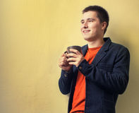 Young business man drinking coffee near the wall Royalty Free Stock Images