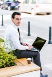 Young Business Man Drinking Coffee While Using Laptop. And Sitting At Bench Royalty Free Stock Images